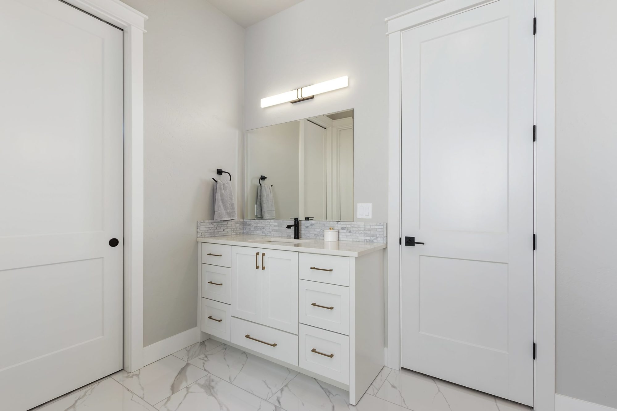 A modern looking bathroom with customs cabinets and doors.